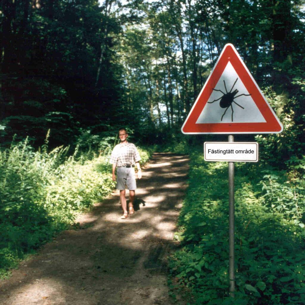 En person står på en stig i ett skogsområde. I förgrunden en skylt som varnar för fästingar.