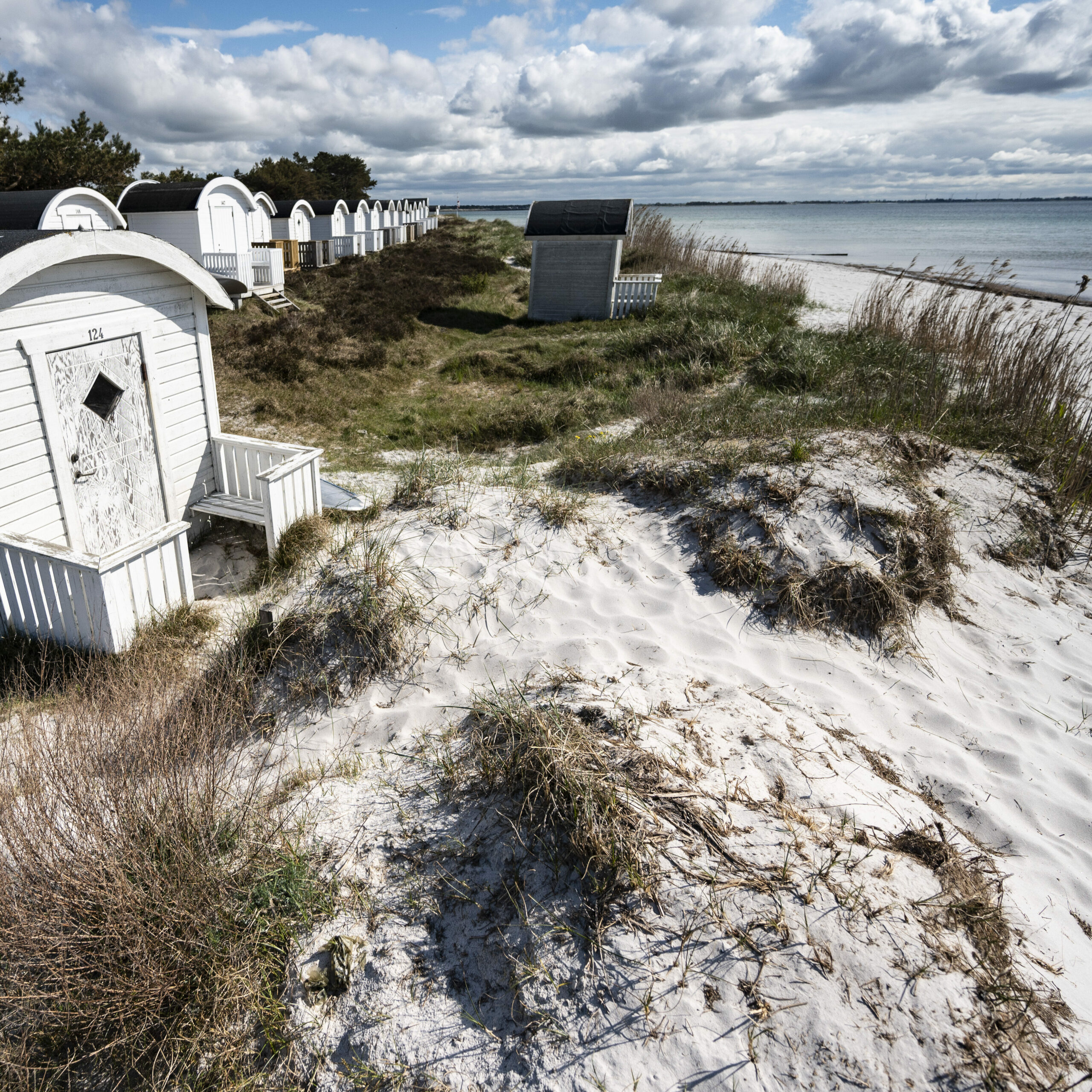 Vita strandstugor på en krtivit strand.