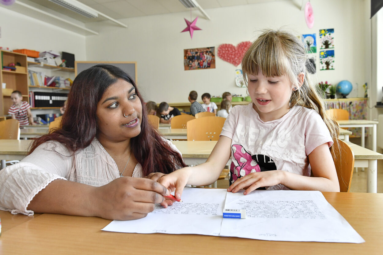 Bild på lärare som hjälper elev i klassrum.