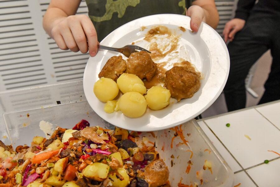 Ett barn skrapar ner potatis och köttbullar i en hink för matavfall.