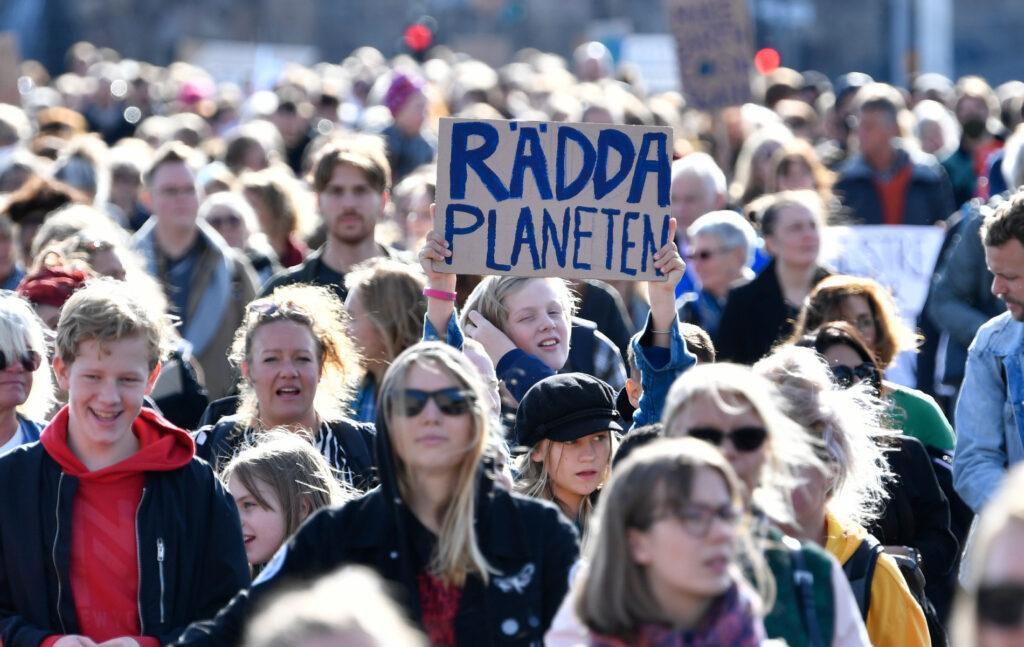 """Barn och vuxna demonstrerar tillsammans. På en skylt står det """"Rädda planeten""""."""