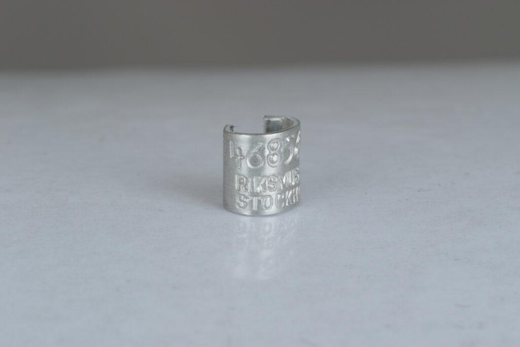 """En liten ring i metall med texten """"Riksmuseet Stockholm""""."""