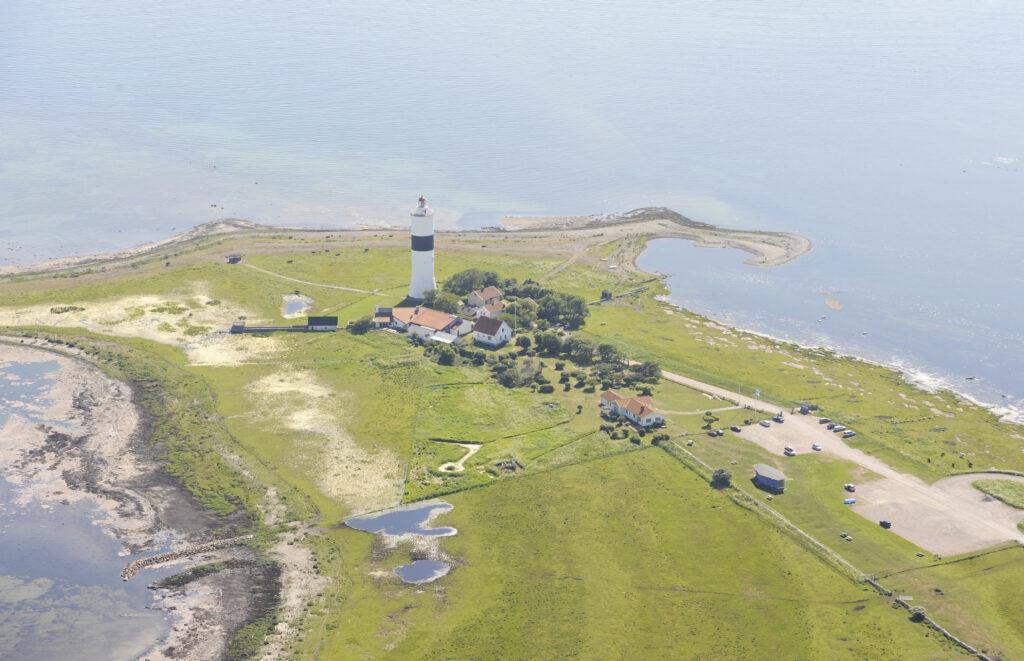 Flygbild över Ottenby fågelstation, på en udde med en fyr och ett par hus i mitten.