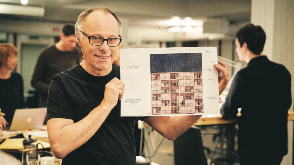 Johan Ehrenberg håller upp ritning på de klimatpositiva hyreshusen.